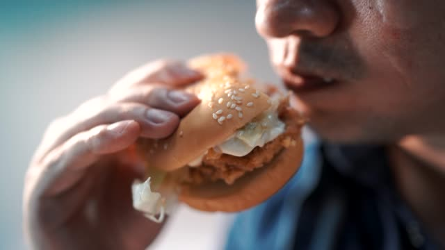 close up shot men are eating hamburgers. happily - human mouth stock videos & royalty-free footage