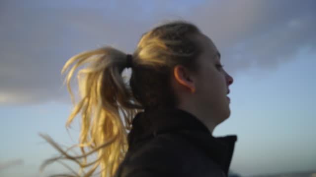 vidéos et rushes de close up shot d'une femme blonde regardant autour du centre-ville de lisbonne près de l'océan - joggeuse