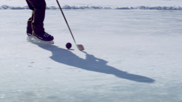 a close up shot of a boy dribbling a hockey puck up and down an ice rink surrounded by snow capped mountains.  half of the shots focus on the stick and the puck and the other half on the upper half of the boys body. - ユタ州 パークシティ点の映像素材/bロール