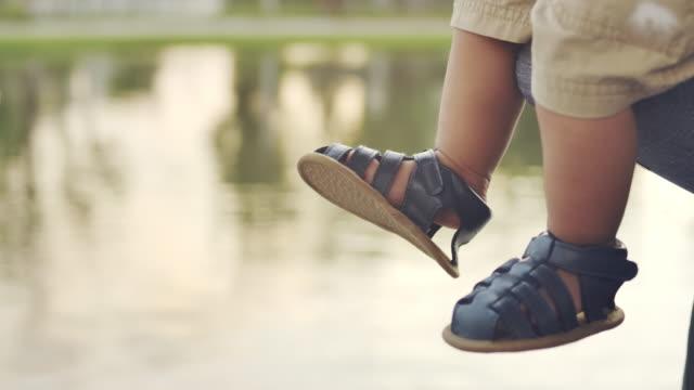 närbild skott av en pojkes fötter i sandle sitter hängande benen på vattnet bakgrunden under dagen - endast en pojkbaby bildbanksvideor och videomaterial från bakom kulisserna