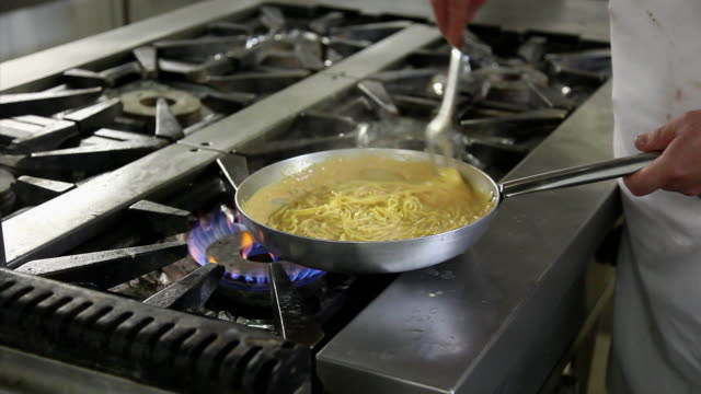 Close up shot of a chef cooking scampi cream spaghetti