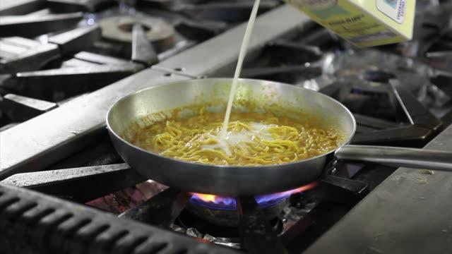 Close up shot of a chef cooking scampi cream spaghetti