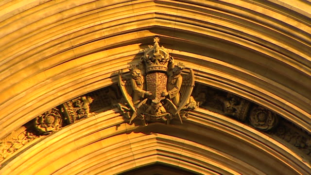 close up shot of a crest featuring three angels above the door to the sovereign's entrance in the palace of westminster london - 庶民院点の映像素材/bロール