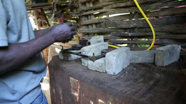 A close up shot of a farmer who is lighting up a selfmade biogas stove that is segregated with several bricks on a plantation near Pilate Haiti