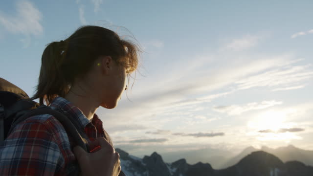 close up shot of a female hiker standing on the edge of a mountain looking into the distance - distant stock videos & royalty-free footage