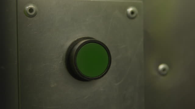 close up shot of a finger pressing a green button on a metal surface - pushing 個影片檔及 b 捲影像
