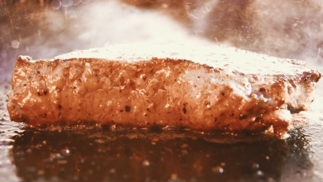slo mo close up shot of a frying steak on a bbq plate - cooking pan video stock e b–roll