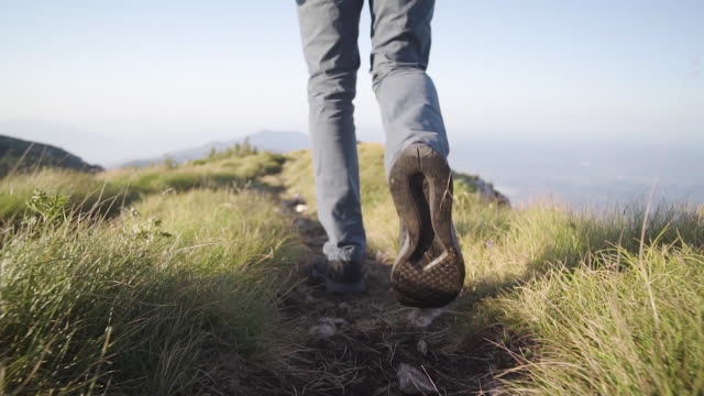 close up shot of a hiker on a mountain path - footpath stock-videos und b-roll-filmmaterial