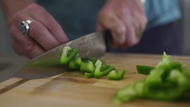 close up shot of a man cutting a pepper on a cutting board in a kitchen - accuracy stock videos & royalty-free footage