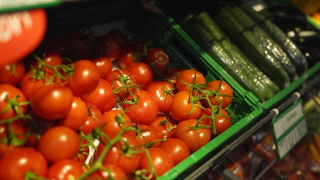 nahaufnahme eines mannes, der tomaten in einem lebensmittelgeschäft abholt - gemüse stock-videos und b-roll-filmmaterial