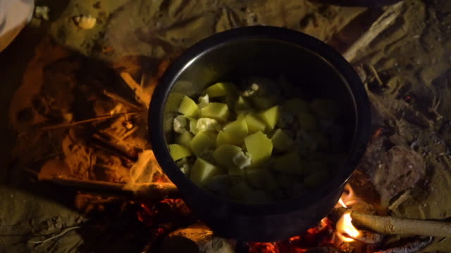 vidéos et rushes de a close up shot of a man pouring vegetables onto a boiling pot over a campfire. - ustensile