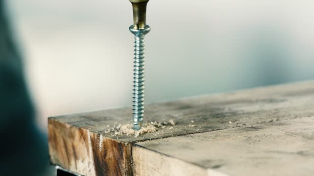 close up shot of a man using an electric hand drilling screw into a wood table - hole stock videos & royalty-free footage
