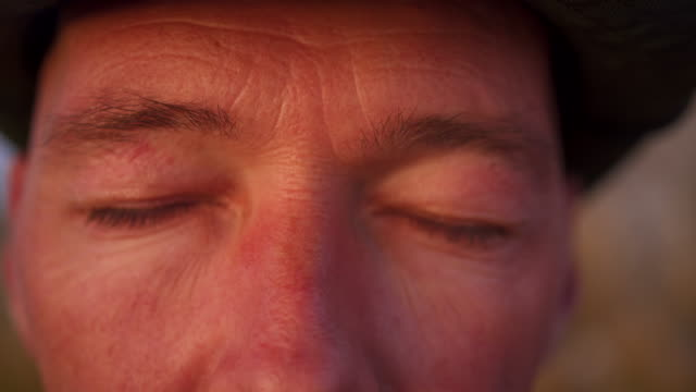 vidéos et rushes de fermez-vous vers le haut du projectile d'un homme avec des yeux de chapeaux - fondu d'ouverture