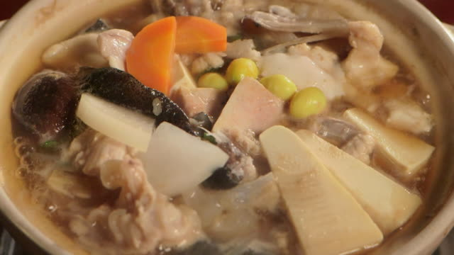 Close up shot of a monkfish hotpot vegetables and diced monkfish meat in a boiling broth