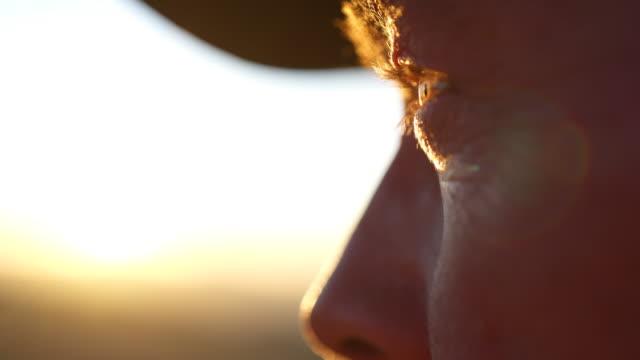 vidéos et rushes de fermez-vous vers le haut du projectile des yeux d'un garde-parc regardant vers le coucher du soleil - chapeau