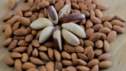 Close up shot of a pile of almonds and brazilian nuts rotating on wooden table