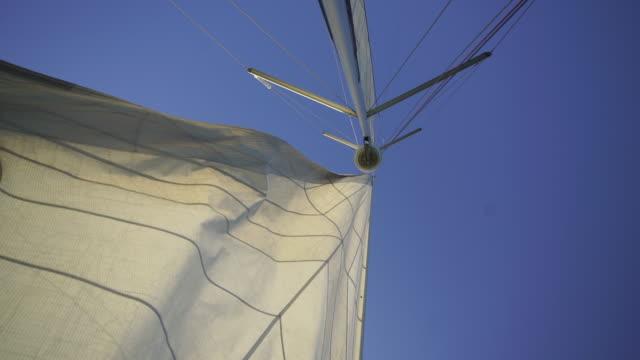 vídeos de stock e filmes b-roll de close up shot of a sailboat mast with blue sky - mastro peça de embarcação