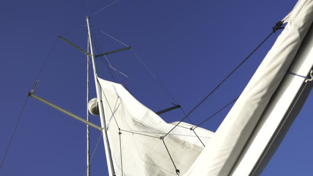 close up shot of a sailboat mast with blue sky - schiffsmast stock-videos und b-roll-filmmaterial