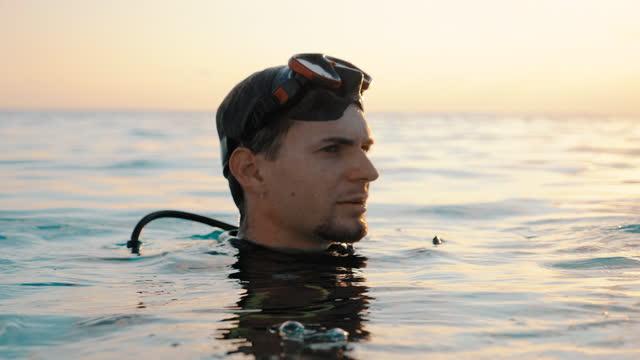 vidéos et rushes de gros plan d'un plongeur émergeant de l'eau au coucher du soleil - discovery