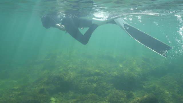 vídeos y material grabado en eventos de stock de tiro de cerca de un buceador nadando cerca de la superficie del océano - escafandra autónoma