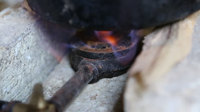 a close up shot of a single burner biogas stove that is lit to heat up a small pot on top of it on a plantation near pilate haiti - hispaniola stock videos and b-roll footage