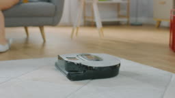 Close Up Shot of a Smart Robot Vacuum Cleaner Sucking Up Dust from a Carpet. Beautiful Couple is Sitting on a Sofa and Talking in the Background. Technological Home Appliance Device Moves Past Them.
