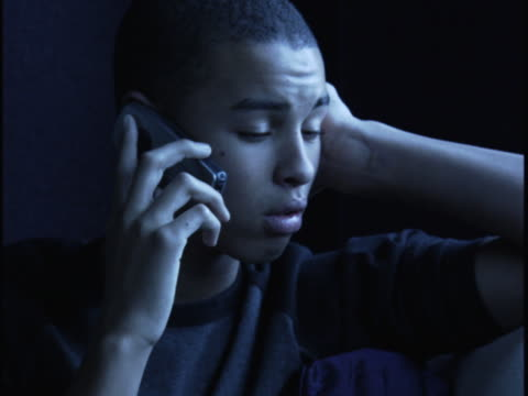 close up shot of a teenage male at night as he talks on a cell phone - one teenage boy only stock videos & royalty-free footage