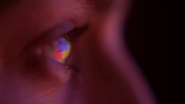 a close up shot of a television screen reflected in a young woman's eye as she watches tv - fernsehserie stock-videos und b-roll-filmmaterial
