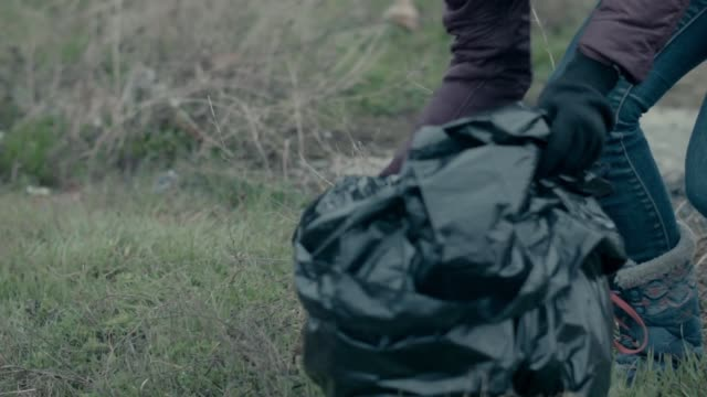 close up shot of a trash bag getting filled with scraps of waste by a volunteer - sevastopol crimea stock videos and b-roll footage