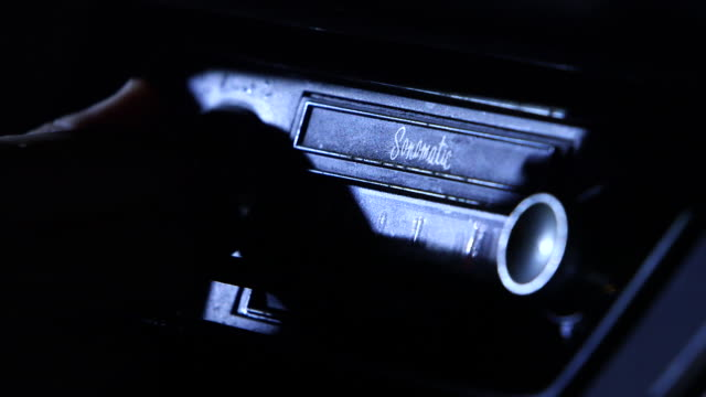 Close up shot of a vintage 1950s car radio, lit by moonlight