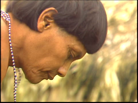 a close up shot of a yanomami indian man hoeing outside a traditional maloca dwelling - yanomami stock videos and b-roll footage