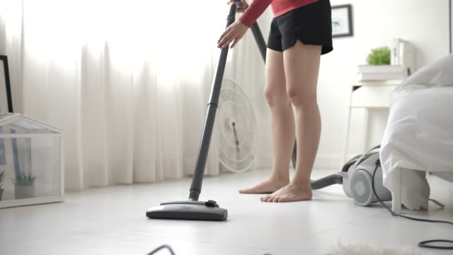 close up shot of a young beautiful woman in casual clothing vacuum cleaning on flooring at home - tidy stock videos & royalty-free footage