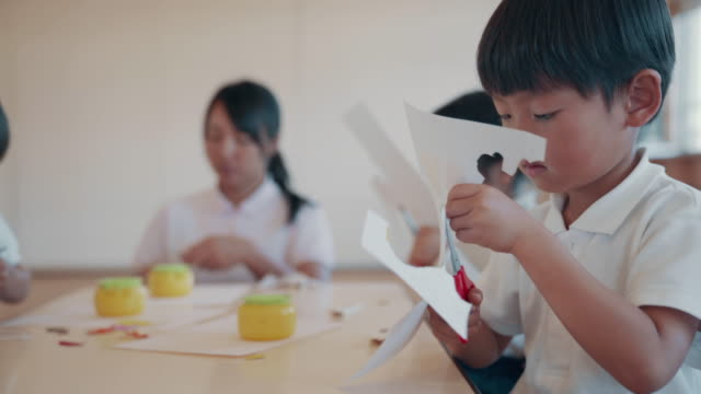 close up shot of a young boy cutting paper in his preschool art class - japanese school uniform stock videos & royalty-free footage