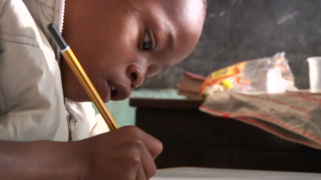 vidéos et rushes de close up shot of a young kenyan student writing school work in class. - gomme
