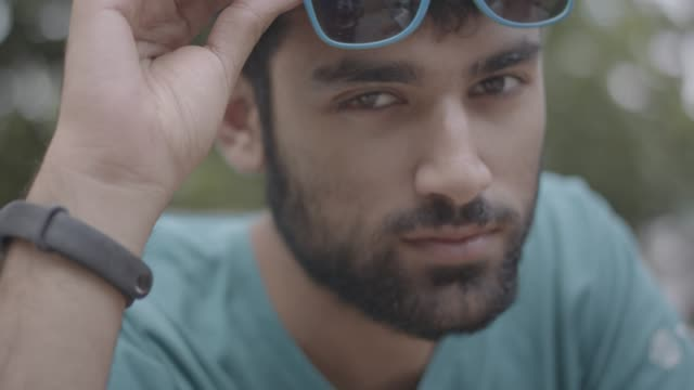 close up shot of a young teenage male looking at camera and playing with sunglasses - beard stock videos & royalty-free footage