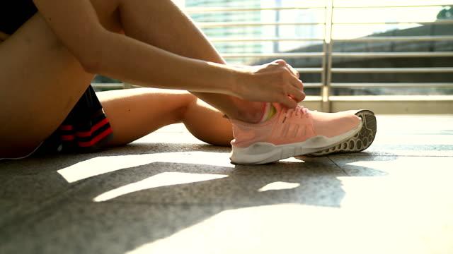vídeos de stock, filmes e b-roll de close-up tiro de um atleta de amarrar seu cadarço de sapato. mulher apertando seus atacadores sentado no chão de manhã. - cadarço