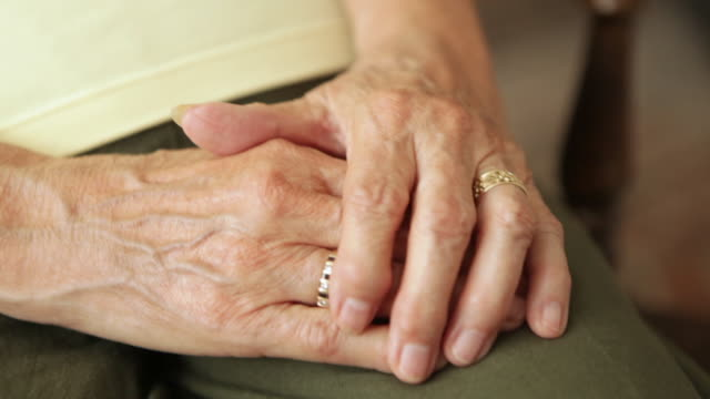 a close up shot of an elderly couple holding hands together. - senior women stock videos and b-roll footage