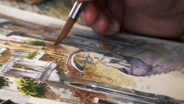 Close up shot of artist painting in details of a scene of a gondola on a canal in Venice.