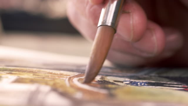 Close up shot of artist painting in details of a watercolor painting.
