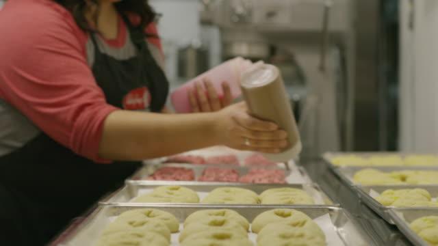 Close up shot of baker squeezing icing onto cookies / Salt Lake City, Utah, United States