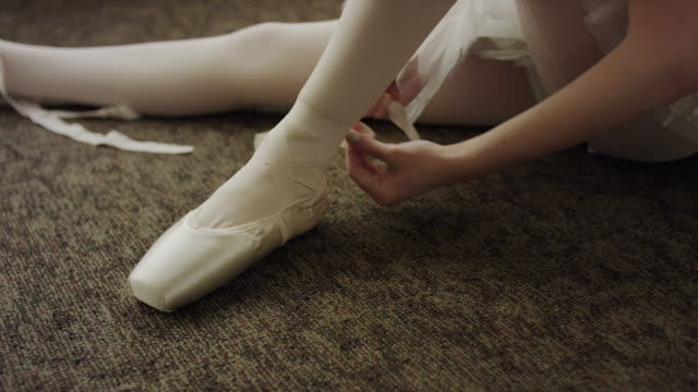 close up shot of ballerina sitting on floor putting on ballet shoe / salt lake city, utah, united states - ballet shoe stock videos and b-roll footage