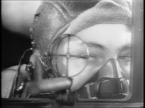 Close up shot of bombardier checking his bomb sight / Close up shots inside the bomber of soldiers surveying the skies through the sights of their...