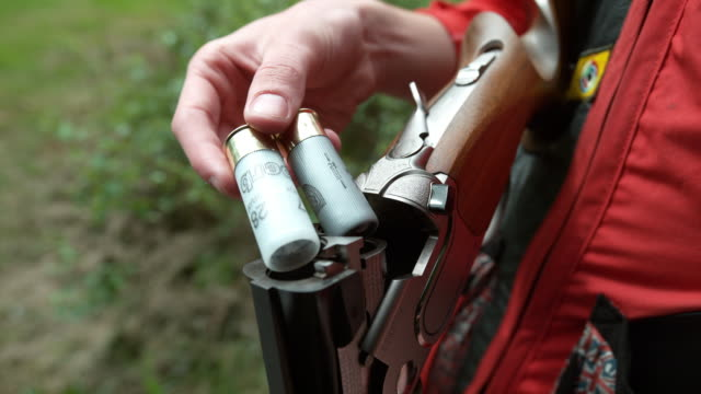 Close up shot of cartridges being loaded into a shotgun