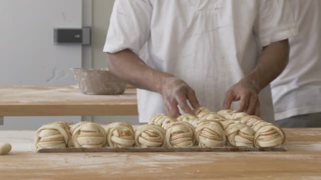 close up shot of cinnamon buns cake being made in cafe in gamla stan, stockholm, sweden, scandinavia, europe - baker occupation stock videos and b-roll footage