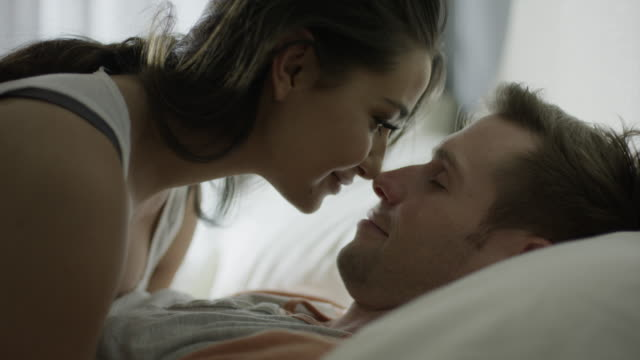 vidéos et rushes de close up shot of couple kissing and nuzzling in bed / cedar hills, utah, united states - lit ameublement