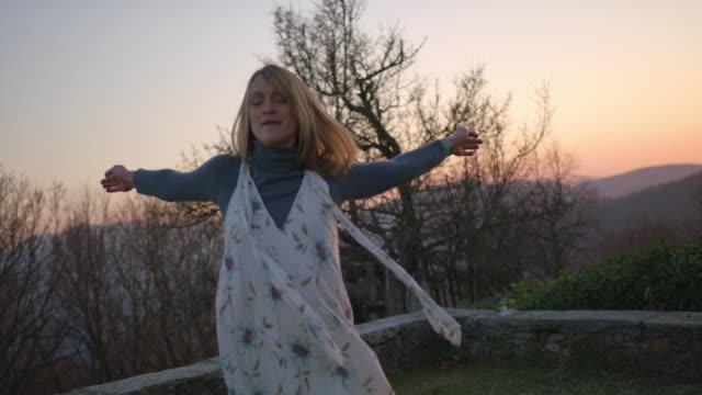 nahaufnahme von tänzer in bewegung, warmer sonnenuntergang himmel hinter ihr - einzelne frau über 30 stock-videos und b-roll-filmmaterial