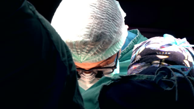 close up shot of doctor in surgery - head stock videos & royalty-free footage