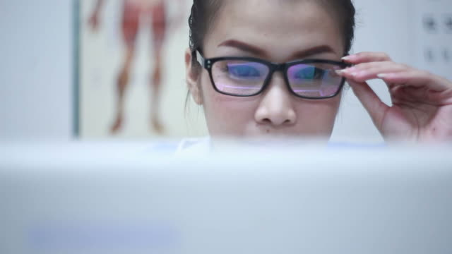 close up shot of doctor wearing glasses using computer - information medium stock videos & royalty-free footage