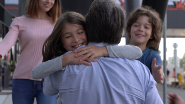 close up shot of excited family hugging picking daddy up at the airport - airport stock videos & royalty-free footage