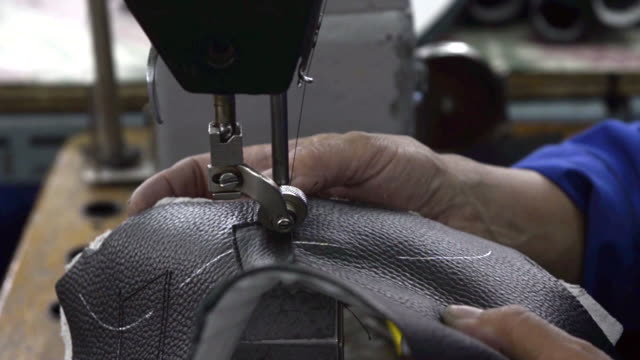 close up shot of factory worker hands sewing together pre cut leather pieces to create boots in factory in mongolia - sewing stock videos & royalty-free footage